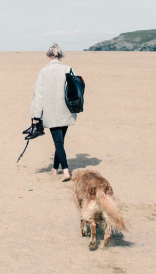 A girl and dog walking on the beach together.