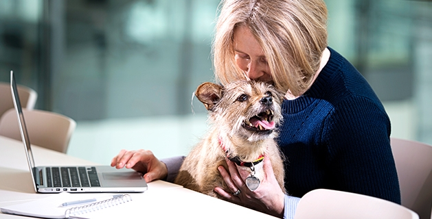 woman with laptop hugging dog